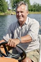 Portrait of happy senior man riding boat on lake
