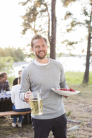 Portrait of happy man holding beer jug and strawberries with friends sitting at picnic table in background 11081008682| 写真素材・ストックフォト・画像・イラスト素材|アマナイメージズ