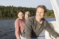 Happy friends travelling on yacht at river