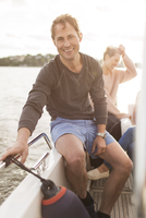 Portrait of happy man sitting on yacht with female friends in background