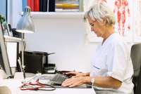 Side view of senior orthopedic surgeon using computer at desk in clinic