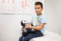 Portrait of boy holding skeleton stuffed toy on examination table at orthopedic clinic