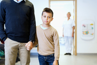 Portrait of boy holding father's hand with nurse in background at orthopedic clinic