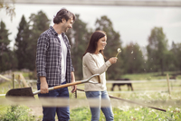 Happy man looking at woman blowing dandelion in organic farm