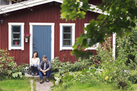 Mid adult couple sitting outside farmhouse