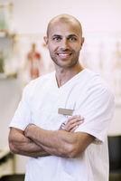 Portrait of confident orthopedic surgeon standing arms crossed in clinic