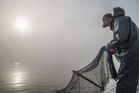 Side view of fisherman working with net on sea in foggy weather