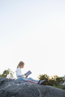 Full length side view of girl doing homework while sitting on rock against clear sky