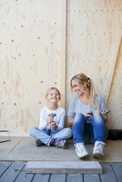 Happy mother and daughter holding hammers against wall of house being renovated