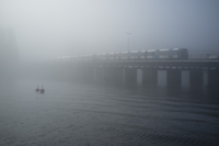 Train passing on railway bridge over sea in foggy weather