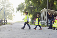 Children in protective jacket with teacher walking on footpath