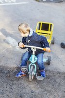 High angle view of boy looking backwards while riding tricycle