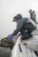 Fisherman pulling fishing net on boat with colleague in background