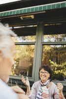 Smiling senior woman gesturing at outdoor cafe