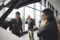 Happy friends looking at car while senior man using phone in showroom