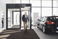 Front view of senior man entering car showroom