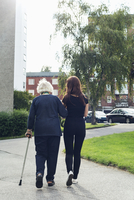 Full length rear view of elderly woman walking with granddaughter on footpath