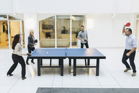 Businesspeople playing table tennis in office