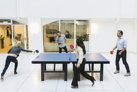 Businesspeople playing table tennis in modern office