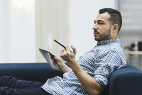 Side view of businessman holding digital tablet while relaxing on sofa at office