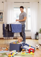 Father drying clothes while looking at baby boy playing with toys