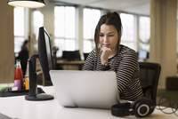 Businesswoman working on laptop at desk in creative office