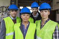 Team of manual workers in protective workwear at factory