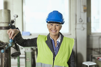 Portrait of happy mature female worker wearing hardhat in factory