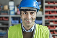 Portrait of happy mature manual worker wearing hardhat in factory
