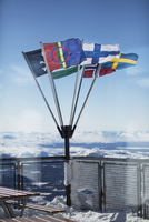 Various flags waving by snow covered mountains