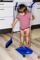Full length of baby girl cleaning floor with broom at domestic kitchen
