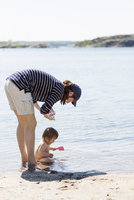 Woman with baby girl playing in sea on sunny day