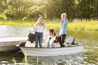 Happy friends with luggage enjoying in boat on lake