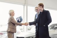 Senior saleswoman shaking hands with man while father looking at him in car dealership shop