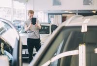 Man photographing car through digital tablet at dealership store