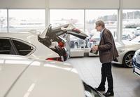 Side view of senior man examining car trunk at showroom