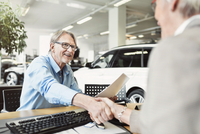 Happy senior man shaking hands with car saleswoman in shop