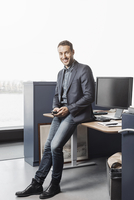 Full length portrait of confident businessman leaning on desk in office