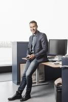 Full length portrait of confident businessman leaning on desk in office 11081010841| 写真素材・ストックフォト・画像・イラスト素材|アマナイメージズ