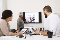Side view of businesswoman giving presentation to colleagues in office 11081010889| 写真素材・ストックフォト・画像・イラスト素材|アマナイメージズ