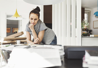 Thoughtful female architect leaning on table at home office