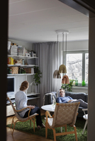 Couple talking while relaxing in living room at home 11081011099| 写真素材・ストックフォト・画像・イラスト素材|アマナイメージズ