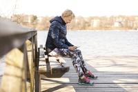 Senior woman in sportswear using phone while sitting on bench by lake 11081011236| 写真素材・ストックフォト・画像・イラスト素材|アマナイメージズ