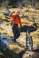 Portrait of man gesturing thumbs up while standing with mountain bike on hill 11081011247| 写真素材・ストックフォト・画像・イラスト素材|アマナイメージズ