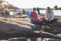 Father and son fishing while sitting on rocks at forest 11081011280| 写真素材・ストックフォト・画像・イラスト素材|アマナイメージズ