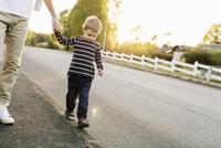 Boy walking with father on empty road 11081011317  写真素材・ストックフォト・画像・イラスト素材 アマナイメージズ