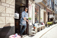 Confident man wearing apron standing at entrance of fabric shop 11081011369  写真素材・ストックフォト・画像・イラスト素材 アマナイメージズ