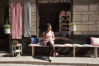 Thoughtful owner having coffee while sitting on table by cushions outside fabric shop 11081011374| 写真素材・ストックフォト・画像・イラスト素材|アマナイメージズ