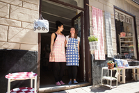 Low angle view of happy female owners standing at entrance of fabric shop 11081011375| 写真素材・ストックフォト・画像・イラスト素材|アマナイメージズ