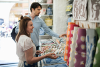 Smiling owner showing fabric swatches to male customer at shop